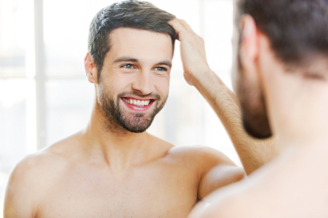 Mann bewundert seine volle Haarpracht nach der Moser-Methode gegen Haarausfall